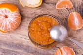 Colorful homemade tangerine jam in glass jar on rustic wooden board