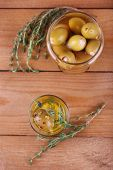 Green olives in oil with spices and rosemary in glass jars on wooden table