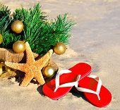 Christmas Tree With Christmas Balls, Slippers And Starfish On The Sand