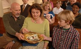 picture of stewardship  - A Sunday morning church congregation putting money in the offering plate - JPG