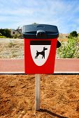 picture of dog poop  - Red dog waste container in a park - JPG