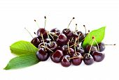 stock photo of black-cherry  - Black ripe cherries with leaves on a white background - JPG