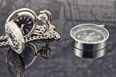 picture of reflection  - pocket watch and compass lying on the reflecting surface - JPG