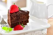 foto of chocolate fudge  - Fresh Home Made Sticky Chocolate Fudge Cake With Strawberries and a jug of pouring cream - JPG