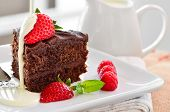 foto of chocolate fudge  - Fresh Home Made Sticky Chocolate Fudge Cake With Strawberries And Raspberries and a jug of fresh pouring cream - JPG