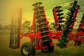 image of cultivator-harrow  - Agricultural equipment in sunset light - JPG