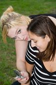 Friends On Cell Phone Together (Beautiful Young Blonde And Brune