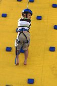 A Child Abseilling Down A Climbing Wall