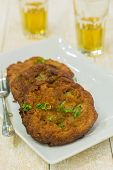 pic of poi  - Crispy fried poi and vegetable patties topped with green onions