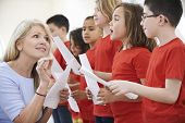 picture of encouraging  - Children In Singing Group Being Encouraged By Teacher