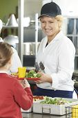 picture of school lunch  - Famale Pupil In School Cafeteria Being Served Lunch By Dinner Lady - JPG