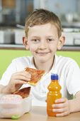 foto of school lunch  - Male Pupil Sitting At Table In School Cafeteria Eating Unhealthy Packed Lunch - JPG