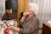 foto of face-powder  - Senior caucasian woman about ninety years old applies face powder before the mirror in her bed room - JPG