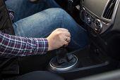 stock photo of gear-shifter  - Closeup shot of young man shifting manual gearbox in car - JPG