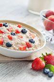 stock photo of porridge  - close up view of oatmeal porridge with berries on color back - JPG