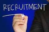 stock photo of recruiting  - Business concept image of a hand holding marker and write Recruitment over blue background - JPG