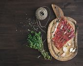 stock photo of pork  - Cured pork meat or prosciutto on a rustic woodem board with garlic spices and thyme over a dark wood background with a copy space - JPG
