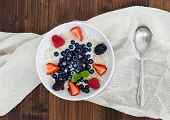 image of porridge  - A bowl of oat porridge with fresh berries honey almond petals and leaves of mint over a piece beige linen fabric on a dark wooden background a view from above - JPG