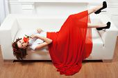 pic of minx  - Girl lying on the sofa her red dress hangs to the floor - JPG