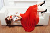 stock photo of minx  - Girl lying on the sofa her red dress hangs to the floor - JPG