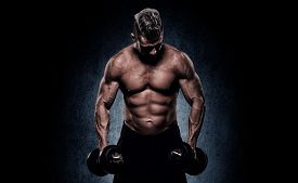 stock photo of bicep  - handsome young man on wall background doing exercises for the biceps - JPG