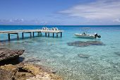 picture of pontoon boat  - White funboat on blue lagoon and wood pontoon - JPG