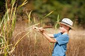 Kid With Straw Hat Playing With Bulrush