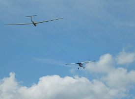 stock photo of glider  - A small aircraft is towing a glider to its required height for unassisted flight - JPG