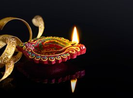 pic of diya  - Colorful clay diya lamp with reflection on black background