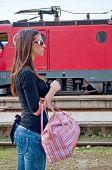 Niña con bolso esperando tren loco en el fondo