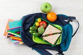 Lunch box with vegetables and sandwich on wooden table. Kids take away food box and school backpack. poster