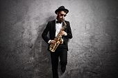 Jazz musician playing a saxophone and leaning against a rusty gray wall poster