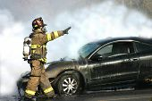 Fireman engulfed in smoke from a car fire.