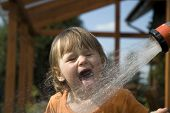 Child Drinking From The Water Hose