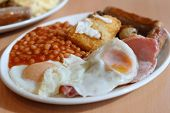 Traditional English breakfast - fried sausages, mushrooms, eggs, bacon, hash browns and tomato baked beens