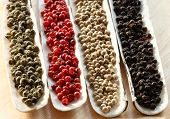 Peppercorns Spices in the sea shells on wood - Black peppercorns, Green peppercorns, Red peppercorns, White  peppercorns