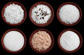 six terracotta plates with different salt - flakes sea salt, coarse sea salt with crashed black pepper, coarse sea salt, fine sea salt, smoked flaky sea salt, table salt, Isolated on black