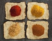 paprika, ginger, curry, tikka masala powders on old paper with burnt edges ,  black stone backdrop