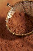 cacao en polvo en el tamiz de estilo rústico plata vieja, dof superficial