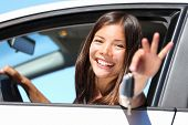 Woman driving showing car keys out the window. Young female driving happy about her new car or drive