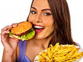 Woman eating french fries and hamburger. Portrait of student consume fast food on table. Girl trying poster