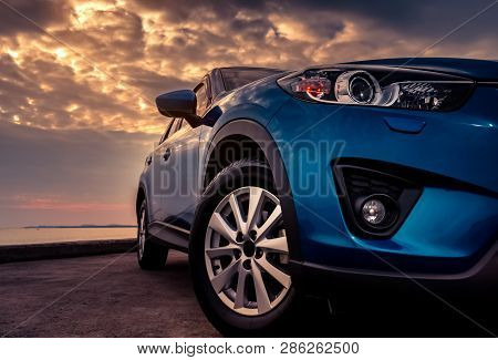 poster of Blue Suv Car With Sport And Modern Design Parked On Concrete Road By The Sea At Sunset In The Evenin