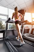 Slim Pretty Woman Running At The Treadmill In The Gym Against The Sunset. Concept Of Cardio Exercise poster