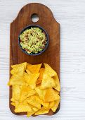 Bowl Of Guacamole With Nachos On Rustic Wooden Board Over White Wooden Background. From Above. Top V poster