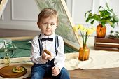 Cute Little Boy In A White Shirt And Tie Sits Near A Tent In His Room And Drinks Homemade Lemonade F poster