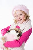 cute teen girl in winter outfit holding rabbit isolated on white