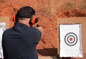 Man shooting at a target on an outdoor shooting range, focus on gun