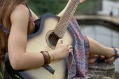 Close Up. Hippie Woman Playing Guitar Near Forest Lake poster