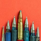 Bullet And Pens On Red Background. Freedom Of The Press Is At Risk Concept. World Press Freedom Day  poster