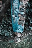 woman legs in embroidered blue jeans boho style and sandals stand in grass summer fashion poster